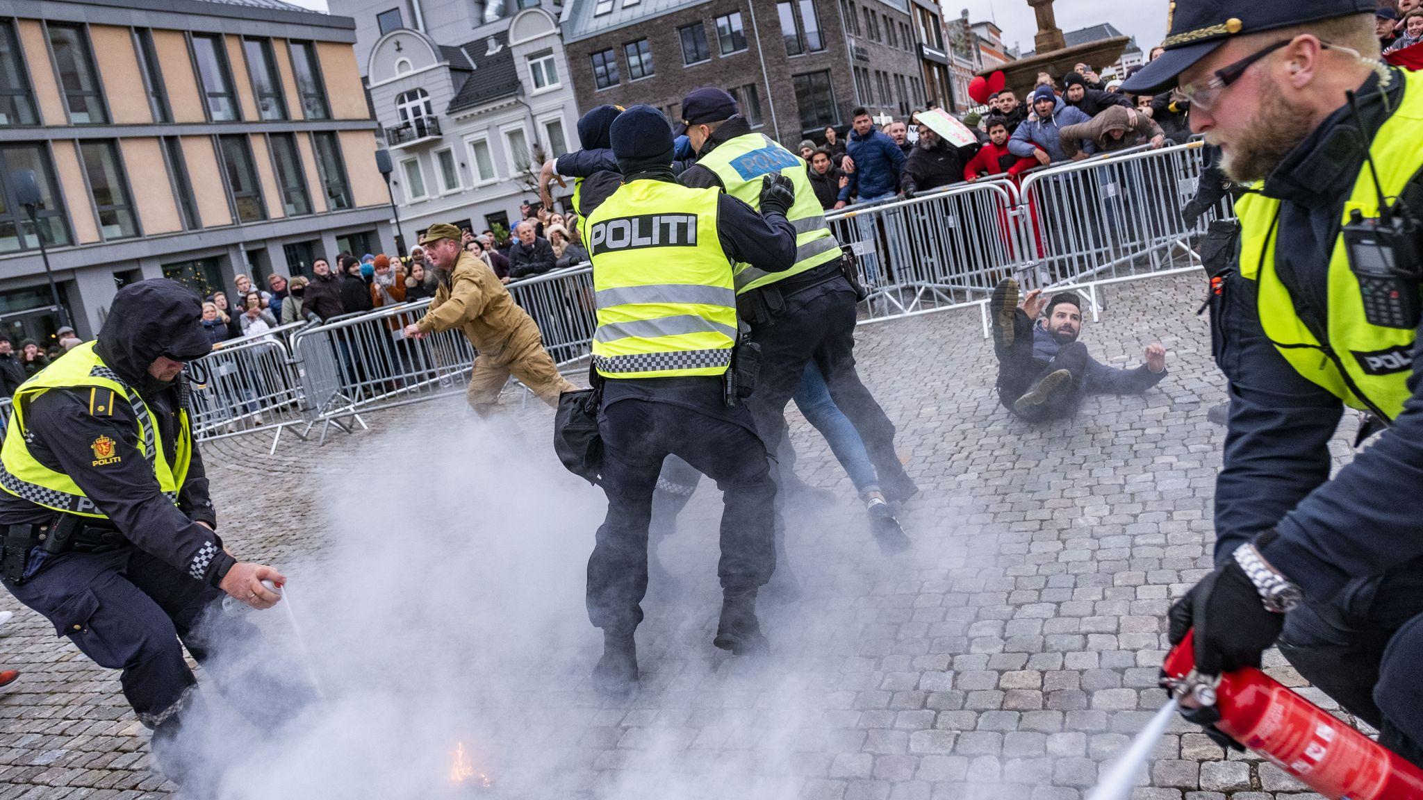 Politiet grep inn da SIAN-leder Lars Thorsen (i beige klær) satte fyr på Koranen under en markering i Kristiansand.